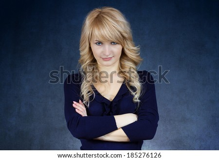 Closeup portrait, skeptical young woman with arms crossed looking suspicious, unconvinced, or you did something wrong, isolated dark blue background. Negative human emotion, facial expression, feeling - stock photo