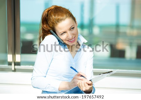 Closeup portrait, smiling attractive successful businesswoman, entrepreneur, corporate employee taking notes, talking on cellphone while walking in company building, isolated background office windows - stock photo