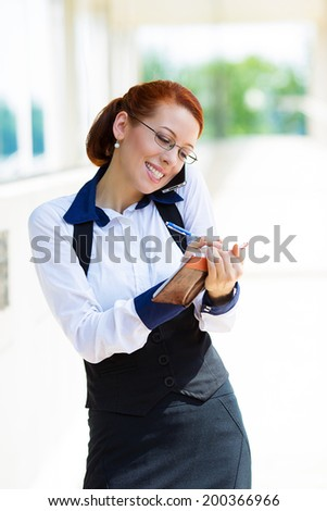 Closeup portrait, smiling attractive successful businesswoman, entrepreneur, corporate employee taking notes, talking on cellphone while walking on street, isolated background city building office - stock photo