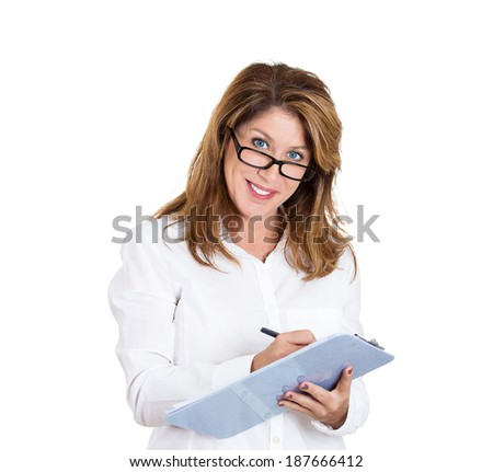 Closeup portrait, smiling, beautiful, mature business woman with black glasses, writing on clipboard with pen, isolated white background. Positive human emotion facial expression feelings