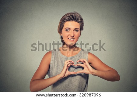 Closeup portrait smiling cheerful happy young woman making heart sign with hands isolated on gray wall background. Positive human emotion expression feeling life perception attitude body language - stock photo
