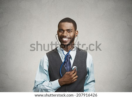 Closeup portrait smiling executive man, business person, worker listening to his heart with stethoscope isolated grey background. Preventive medicine, financial condition concept. Face expressions - stock photo