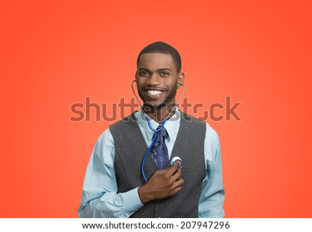 Closeup portrait smiling executive man, business person, worker listening to his heart with stethoscope isolated red background. Preventive medicine, financial condition concept. Face expressions - stock photo