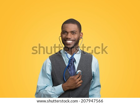 Closeup portrait smiling executive man, business person, worker listening to his heart with stethoscope isolated yellow background. Preventive medicine, financial condition concept. Face expressions - stock photo