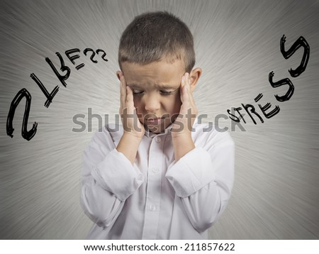 Closeup portrait stressed child, boy hands on temples, head spinning around, overwhelmed at school in life, isolated grey wall background. Human facial expressions, emotions, feeling, perception - stock photo