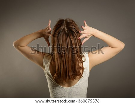 Closeup portrait stressed, frustrated angry woman pulling hair out yelling screaming temper tantrum isolated on grey wall background. Negative human emotion expression reaction attitude - stock photo
