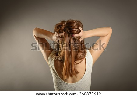 Closeup portrait stressed, frustrated angry woman pulling hair out yelling screaming temper tantrum on grey wall background. Negative human emotion expression reaction attitude - stock photo