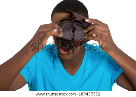 Closeup portrait, stressed, upset, sad, unhappy young man standing with, looking into hole of empty wallet, isolated white background. Financial difficulties, bad economy concept. Negative emotion - stock photo