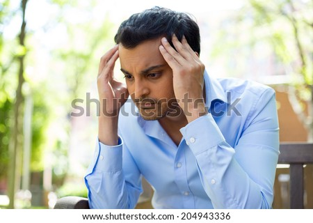 Closeup portrait, stressed young business man, hands on head with bad headache, isolated background of trees outside. Negative human emotion facial expression feelings. - stock photo