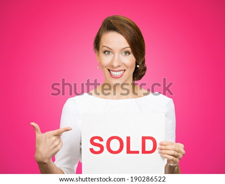 Closeup portrait, super happy excited successful young business woman holding, pointing to red sold sign, isolated pink background. Positive emotion feeling. Financial reward - stock photo