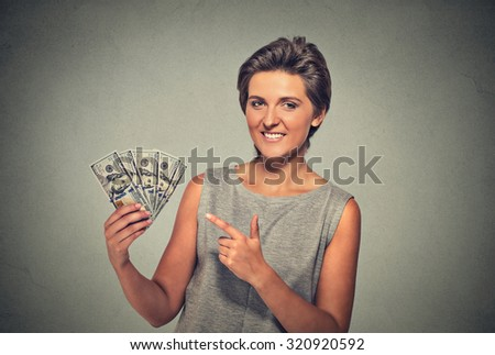 Closeup portrait super happy excited successful young woman holding money dollar bills in hand isolated on gray wall background. Positive human emotion facial expression feeling. Financial reward