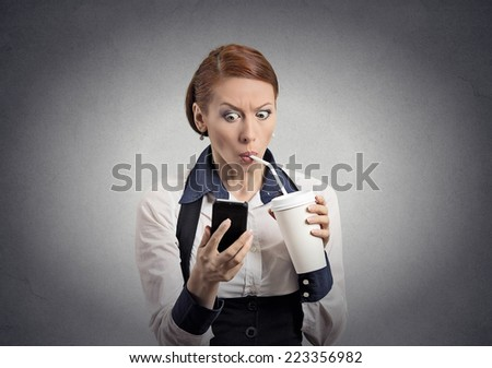 Closeup portrait surprised business woman reading breaking news on smart phone holding mobile drinking soda coffee isolated grey wall background. Human face expression, corporate executive emotions - stock photo
