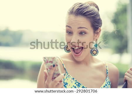 Closeup portrait surprised screaming young girl looking at phone seeing news or photos with funny emotion on her face isolated outside city background. Human emotion, reaction, expression  - stock photo