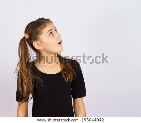 Closeup portrait surprised, shocked young, little girl looking carefully side way, isolated grey background space to right. Human emotions, facial expressions, feelings, attitude - stock photo
