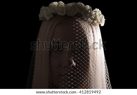 Closeup portrait. The face of a young woman in a veil with a wreath of roses on her head. Black background - stock photo