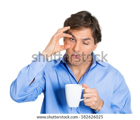 Closeup portrait tired, falling asleep business man in blue shirt holding cup coffee, struggling not to crash, stay awake, keep eyes opened isolated white background. Human emotion, facial expressions