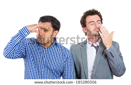 Closeup portrait, two business men, corporate workers, friends, one pinching nose something stinks, second in gray suit smelling something nice, isolated white background . Emotion contrast.