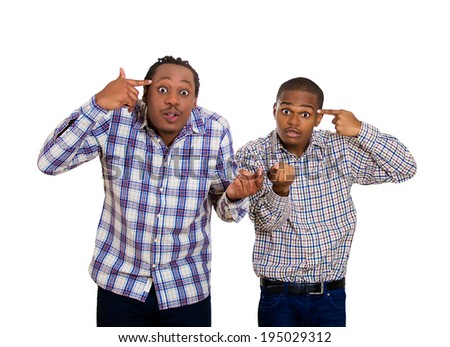 Closeup portrait two rude, difficult, angry young men gesturing with fingers against temples, are you crazy? Isolated white background. Negative human emotions, facial expressions, feelings, reaction - stock photo