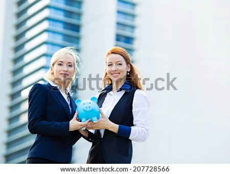 Closeup portrait two smiling business women bank employee, customer holding piggy bank depositing money isolated corporate office background. Financial saving banking concept. Positive face expression - stock photo