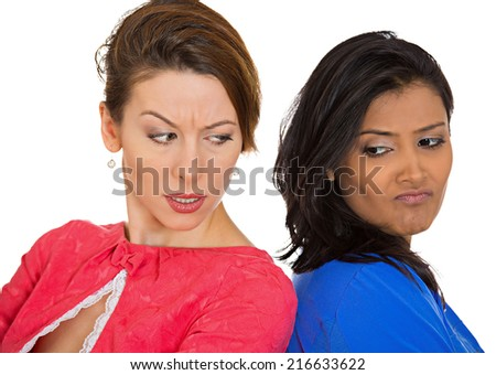 Closeup portrait two unhappy, angry girls, back to back, sad disappointed hate each other isolated white background. Negative human emotion facial expression, feeling, body language conflict situation - stock photo