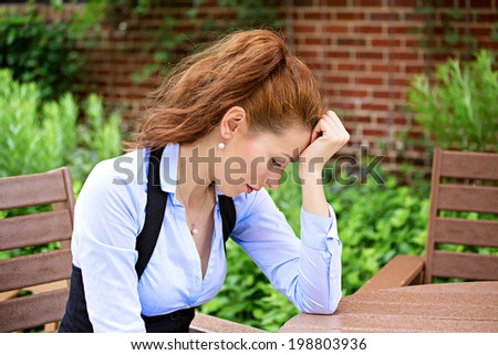 Closeup portrait unhappy business woman, head on hand sitting in armchair bothered by mistake having bad headache isolated background outdoor office campus. Negative human emotions, facial expressions - stock photo