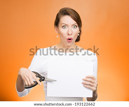 Closeup portrait unhappy, confused, surprised, shocked business woman, funny looking female, worker employee cutting blank white paper, copy space, scissors isolated orange background. Face expression - stock photo