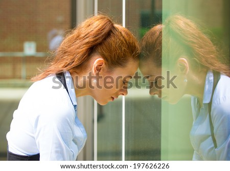 Closeup portrait unhappy young business woman, head on window, bothered by mistake having bad headache isolated background corporate office. Negative human emotion, facial expression feeling reaction - stock photo