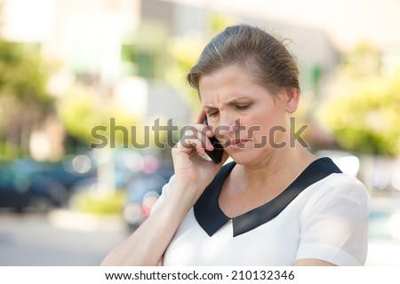Closeup portrait upset, sad, depressed, unhappy, worried brunette woman talking on phone, isolated outdoors background. Negative human emotions, facial expressions, feelings, life reaction. Bad news. - stock photo