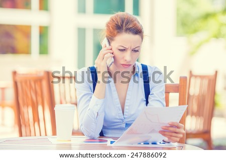 Closeup portrait upset sad, skeptical, unhappy, serious woman talking on phone holding looking at documents outside corporate office background. Negative human emotion face expression feeling reaction - stock photo