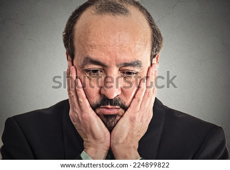 Closeup portrait very sad, depressed, alone, disappointed upset man resting his face on hand looking down isolated on grey wall background. Human mood expression, emotions, feeling, life perception