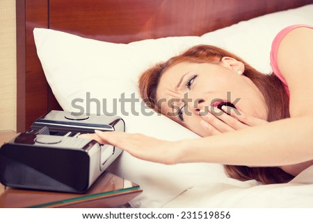 Closeup portrait woman extending hand to alarm clock yawning lies in bed trying to wake up for new day. Human face expression, emotion, feeling. Sleep deprivation, lack of adequate sleep concept - stock photo