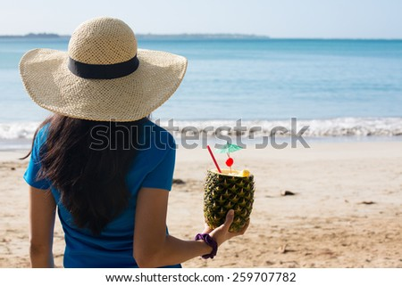 Closeup portrait, woman in blue shirt and brown hat holding pina colada rum pineapple mixed drink with straw and tiny umbrella, while looking out towards beach and ocean - stock photo