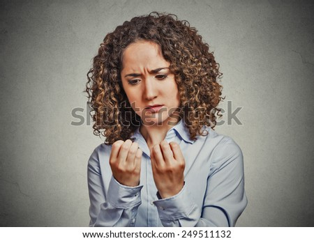 Closeup portrait worried woman looking at hands fingers nails obsessing about cleanliness isolated grey wall background. Negative human emotion facial expression feeling body language perception  - stock photo