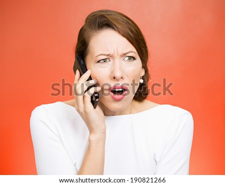 Closeup portrait young angry business woman, corporate employee talking on cell phone, having unpleasant, bad conversation, isolated red background. Negative emotions, facial expressions, reaction - stock photo
