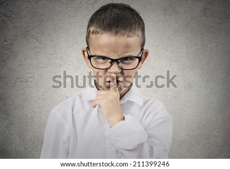 Closeup portrait young angry child, boy placing finger on lips as if to say, shhh, be quiet, silence, isolated grey wall background. Facial expression, human emotions, signs, symbols, body language - stock photo