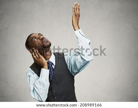 Closeup portrait young angry mad unhappy stressed man covering his ears looking up, to say stop making loud noise it's giving me headache isolated grey background. Negative emotion, face expression - stock photo