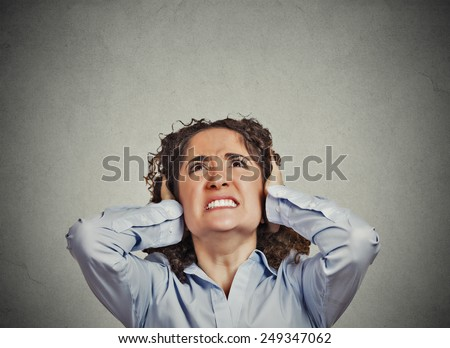 Closeup portrait young angry unhappy stressed woman covering her ears looking up stop making loud noise it's giving me headache isolated grey wall background. Negative emotion face expression feeling  - stock photo