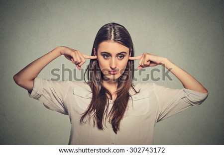 Closeup portrait young angry unhappy woman with closed ears looking away annoyed by loud noise giving her headache ignoring isolated on gray wall background. Negative emotion perception attitude - stock photo
