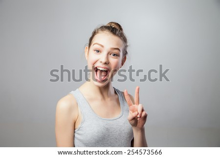 Closeup portrait young attractive blonde woman, student, beautiful girl with v fingers move, isolated grey background. Positive human emotions, face expressions, attitude - stock photo