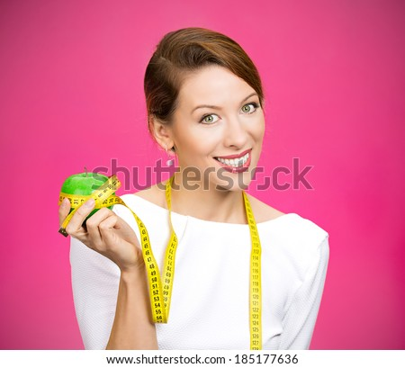 Closeup portrait young attractive, happy, fit woman in white dress, holding apple, measuring tape wrapped around, isolated pink background. Healthy life style, nutrition. Positive emotion, expression - stock photo