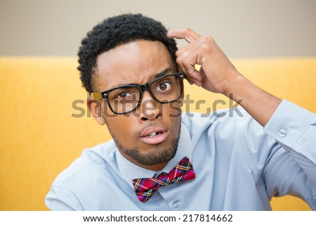 Closeup portrait, young befuddled, bewildered computer geek with big black glasses and bow tie, scratching head wondering about something. - stock photo