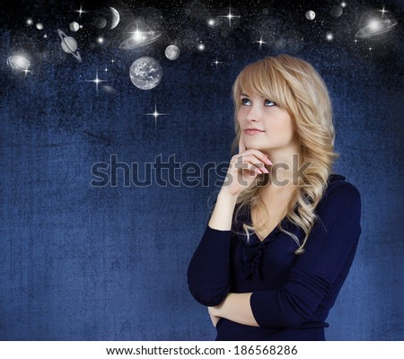 Closeup portrait young blonde woman dreaming, thinking about future, life on other planets, isolated gray-white space background with stars. Emotion, facial expression, feelings, attitude, perception - stock photo