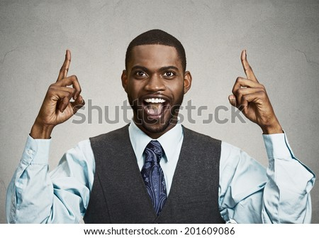 Closeup portrait young business man pointing up  having idea, solution, showing with index finger number one, isolated black grey background. Positive human emotions, facial expressions, symbols, sign - stock photo