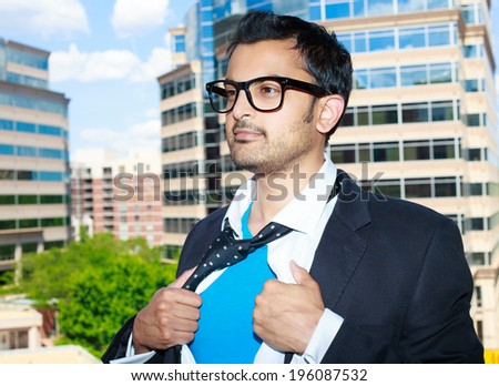 Closeup portrait, young business man with black glasses opening white shirt to show blue superhero outfit inside, ready to fight crime, isolated city buildings trees background - stock photo