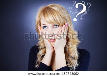 Closeup portrait young business woman, student looking upwards, hands on face, thinking about problem. Isolated on blue grey background, question mark above head. Human emotions, facial expressions - stock photo