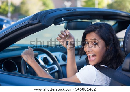 Closeup portrait, young cheerful, joyful, smiling, gorgeous woman holding up keys to her first new sports car. Customer satisfaction - stock photo