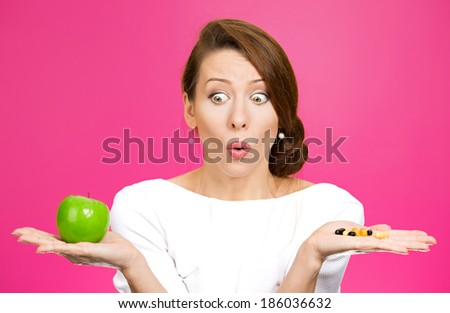 Closeup portrait young confused, puzzled woman holding green fresh apple in one hand, pill, vitamins in another, trying to decide which choice is the best one. Face expressions, emotions, health care - stock photo