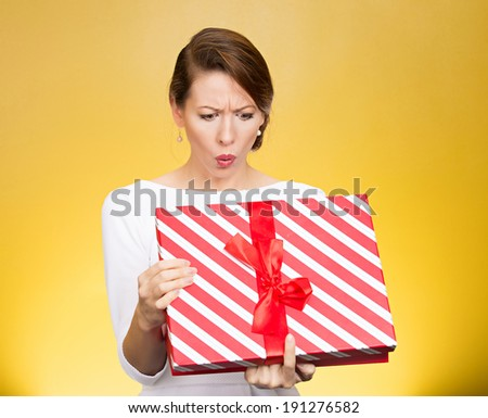 Closeup portrait young funny woman holding opening gift box, surprised, shocked with unexpected present received, isolated yellow background. Sudden human emotion, facial expression, feeling, reaction - stock photo