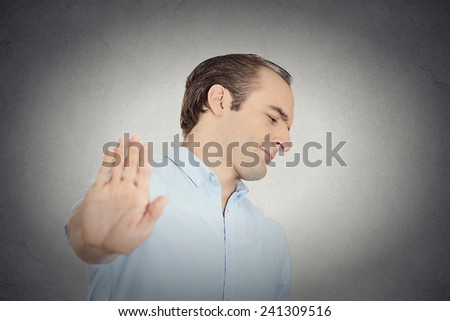 Closeup portrait young handsome grumpy man with bad attitude giving talk to hand gesture with palm outward isolated grey wall background. Negative emotion, facial expression feelings body language - stock photo