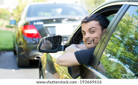 Closeup portrait, young handsome man in his new black car, relaxing, resting face on arms, isolated on outdoors background with vehicle. - stock photo